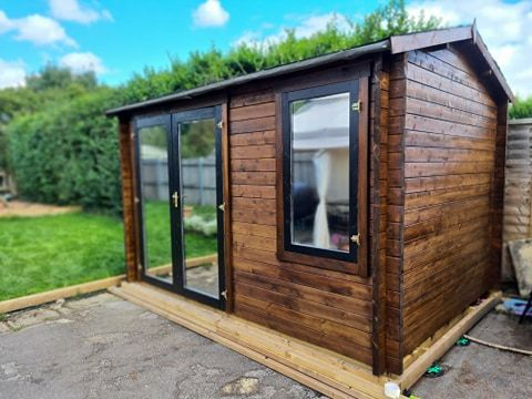timber log cabin with double glass doors on a wood base