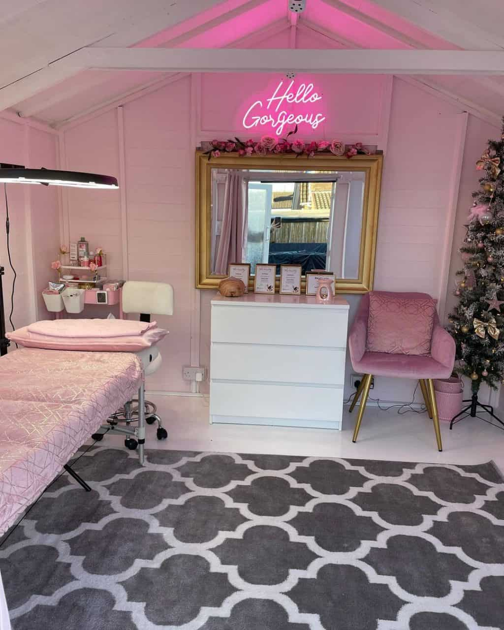 Interior of BillyOh Holly Tongue and Groove Apex Timber Summerhouse home salon with bed, chair, chest of drawers, rug, and pink neon sign