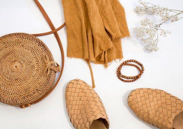 tan fabric, bag, bracelet, and shoes on a white surface with flowers