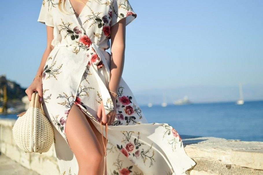 woman wearing a white and floral dress with the sea in the background