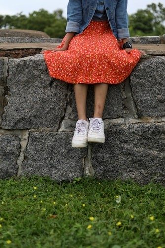 woman in an orange dress and denim jacket sitting on a stone wall