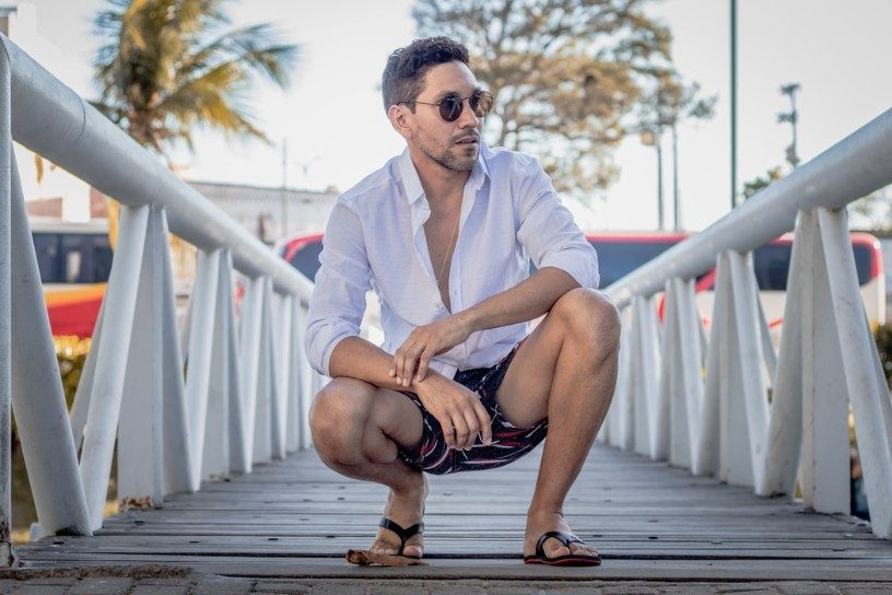 crouching man on a bridge in shirt and sunglasses