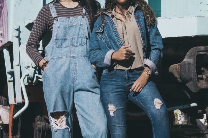 two people wearing denim in front of a truck