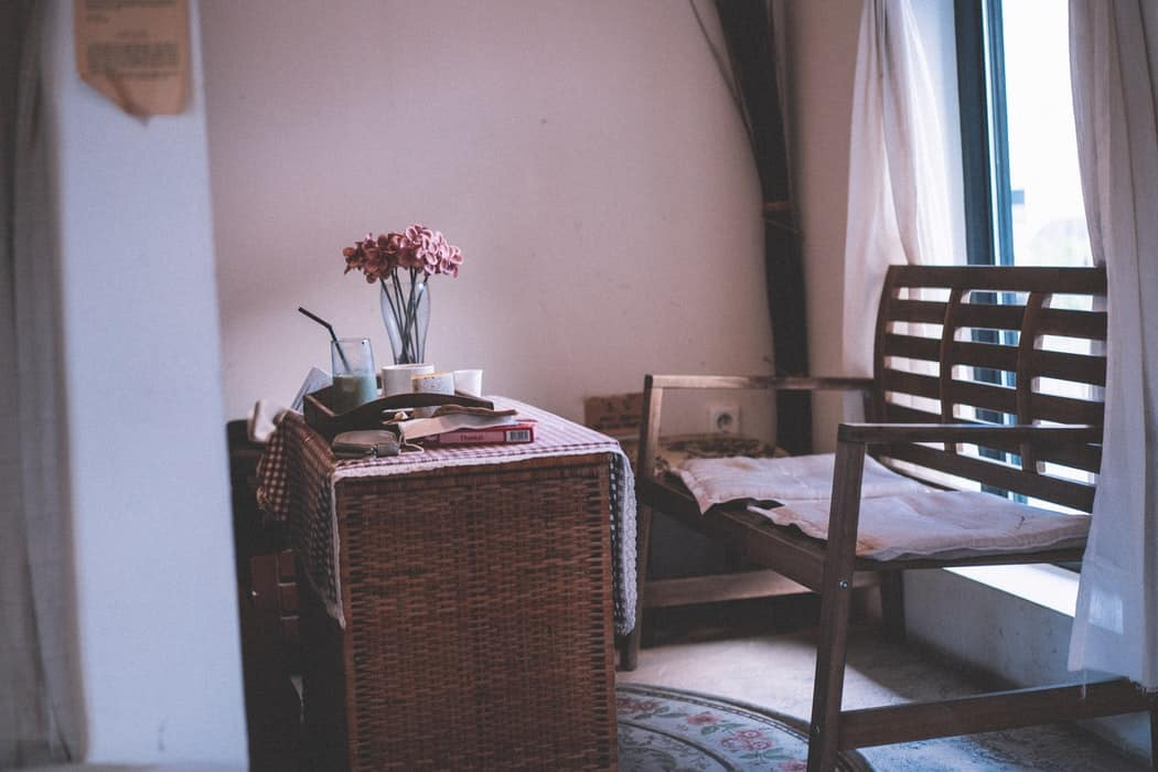 Wooden table with cups and flowers in a vase next to a bench in a room with drawn curtains