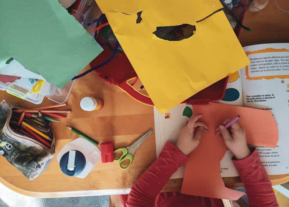 Kids at a table with crafts, pens and paper