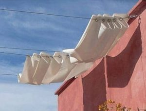 a rollable white canopy on some strings attached to a red wall that looks like a shower curtain but can provide shade or sun at the owners will