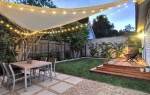 string lights along the perimeter of a triangular canopy that is covering a table and chairs in a garden