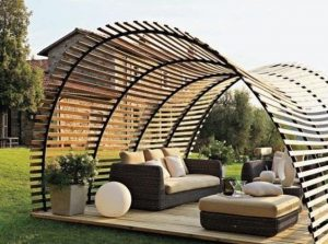 a half-cylinder on it's side with wooden plank cladding with gaps in between the planks to provide shade and sunlight at the same time, covering some garden furniture such as a sofa and a table in the middle of a garden