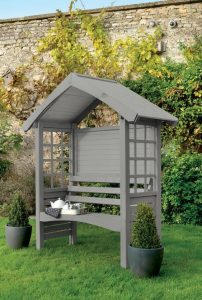 a grey bench in a little birds house type shelter with a roof and a wall at the back but no wall at the front