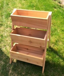 three wooden bin-like troughs stacked on top of one another in a sunny garden