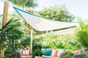 a white triangular sheet which is quite transparent allowing light in but reducing heat over some colourful cushions on an outdoor sofa in a tropical garden