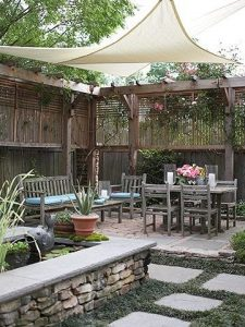 a dark wooden old looking trellis in a japanese-style garden with stepping stones and stone decking with some concrete groundwork and a table, chairs, plantpots and a beige cloth covering the area to create shade.
