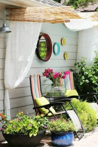 canopy covering two deck chairs in a garden with some colourful mirrors hanging from the wall above and covered by a pair of thin satin curtains held up by some wooden wood bamboo rolls.