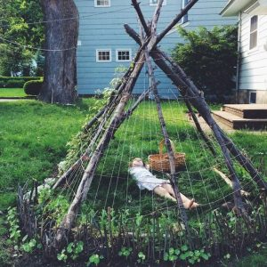 a teepee/wigwam made out of long wooden sticks from trees all slanted diagonally and meeting in the middle, with a child underneath with a woven basket. the teepee has spider web like strings woven around it to create a shelter and climbing plants climbing up it and a light blue house in the background and it is on some grass
