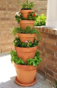 different sized plant pots stacked from the biggest on the ground to the smallest at the top, full with plants