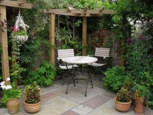 a corner shaped pergola made out of wooden beams set on some concrete patio with some garden table and chairs and lots of plants and greenery and a hanging basket.