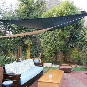 a large black tarpaulin sail covering a whole garden including a dark brown sofa, a light brown table and lots of plants in the background
