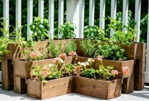 different sized tiered troughs in the corner of a garden with a small medium and large each filled with plants