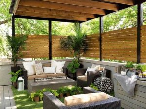 a garden with some rattan chairs, a coffee table, fake grass and a corner style pergola with some woven wood design and light still being allowed through.