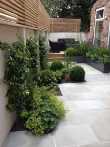 fencing above white stone walls covered in climbing plants and moss on a stone patio in a posh garden