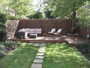 trees covering decking with rattan outdoor furniture such as chairs, tables and a sofa on it with some stepping stones leading up to it from a nice mowed lawn.