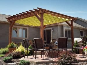 yellow tarpaulin/cloth/material suspended high off the ground on a large wooden pergola, covering a table and chairs outside a large house