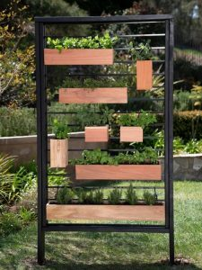 different sized rectangular planters filled with plants both horizontal and vertically hung off a metal square coathanger shaped railing