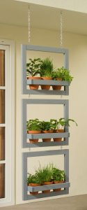two grey hanging rectangle frames each with a row of three small plant pots in them held in by a seatbelt like grey pole hanging from chains
