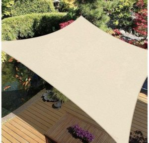 a square beige piece of cloth known as a sail canopy covering some decking