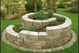 a spiral expensive looking herb garden with bricks layered up in a circular, cylinder formation with plants at the top and bottom in a modern fashion