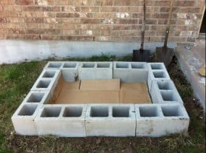 a rectangular flower bed made with a boundary/border of grey breezeblocks stacked next to each other and with some cardboard laid on the ground inside for plants and herbs to be planted and grown