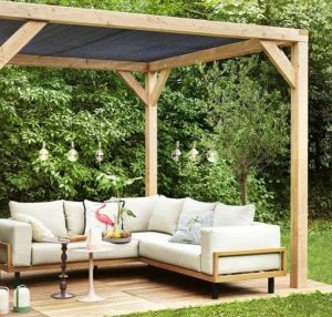 a pergola or canopy with some tarpaulin/a sheet of cloth draped on top to protect the garden furniture underneath and the belongings from the sun and anyone who's sitting there