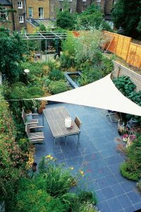 a triangular piece of cloth covering a blue patio with a table, chairs and furniture underneath in a floral garden with a pond and lots of leaves, plants and bushes
