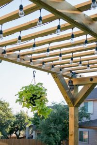 lightbulbs hanging down from a wooden pergola with slats spanning the width of the roof