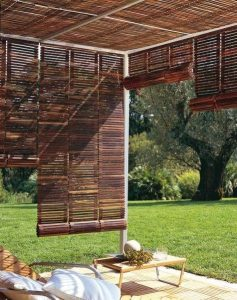 brown mahogany wooden pieces of material acting as blinds for some garden furniture in a garden making for a shady area