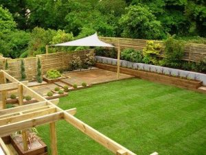 a triangular sail canopy in the corner of a garden covering some decking and creating shade