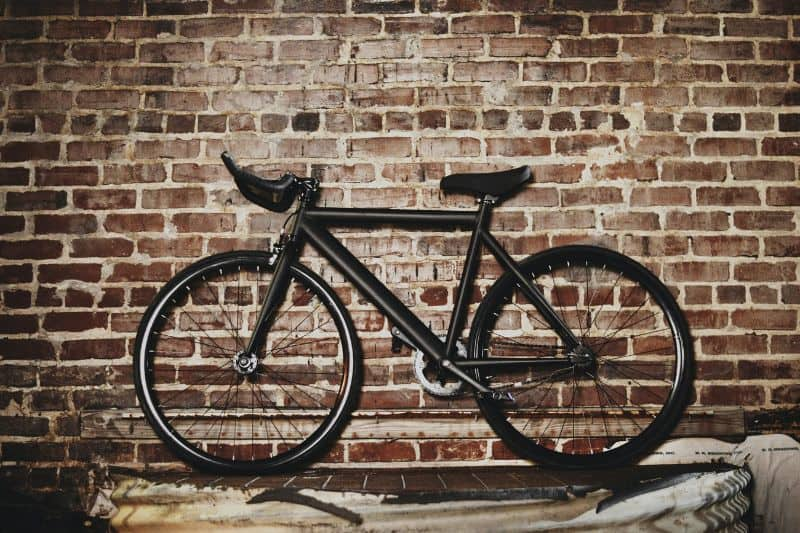 bike suspended against brick wall