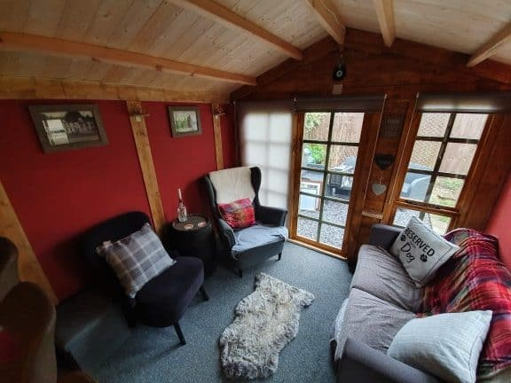 log cabin summerhouse interior with armchairs and sofa