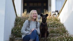 Sam Stanley of A Coastal Plot sat on steps with her dog