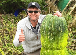 Dan of Allotment Diary with a large vegetable smiling and giving a thumbs up