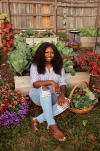 Jasmine Jefferson of Black Girls With Gardens sat smiling surrounded by flowers and planters