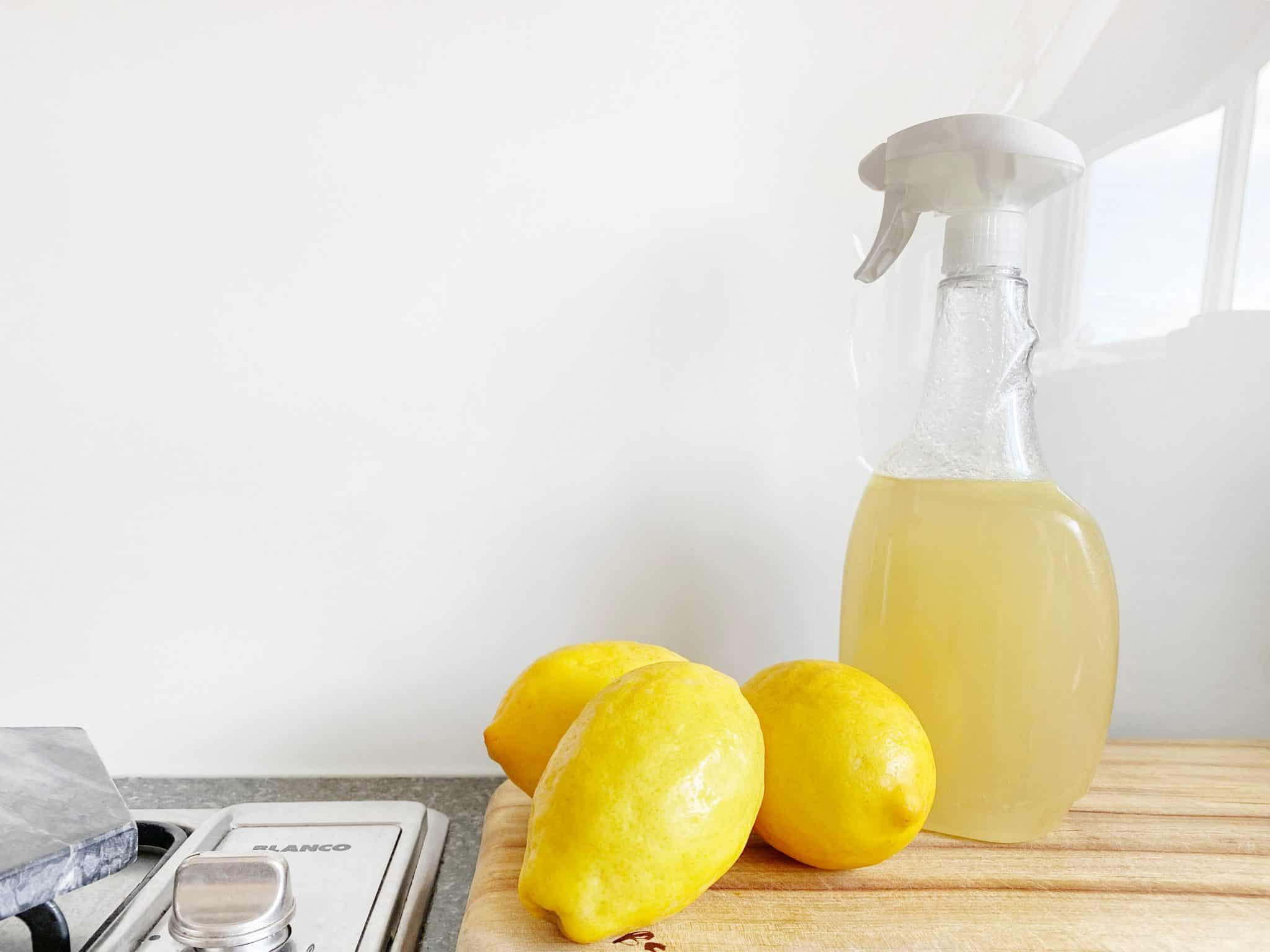 Cleaning Spray Bottle filled with lemon juice and lemons on a chopping board