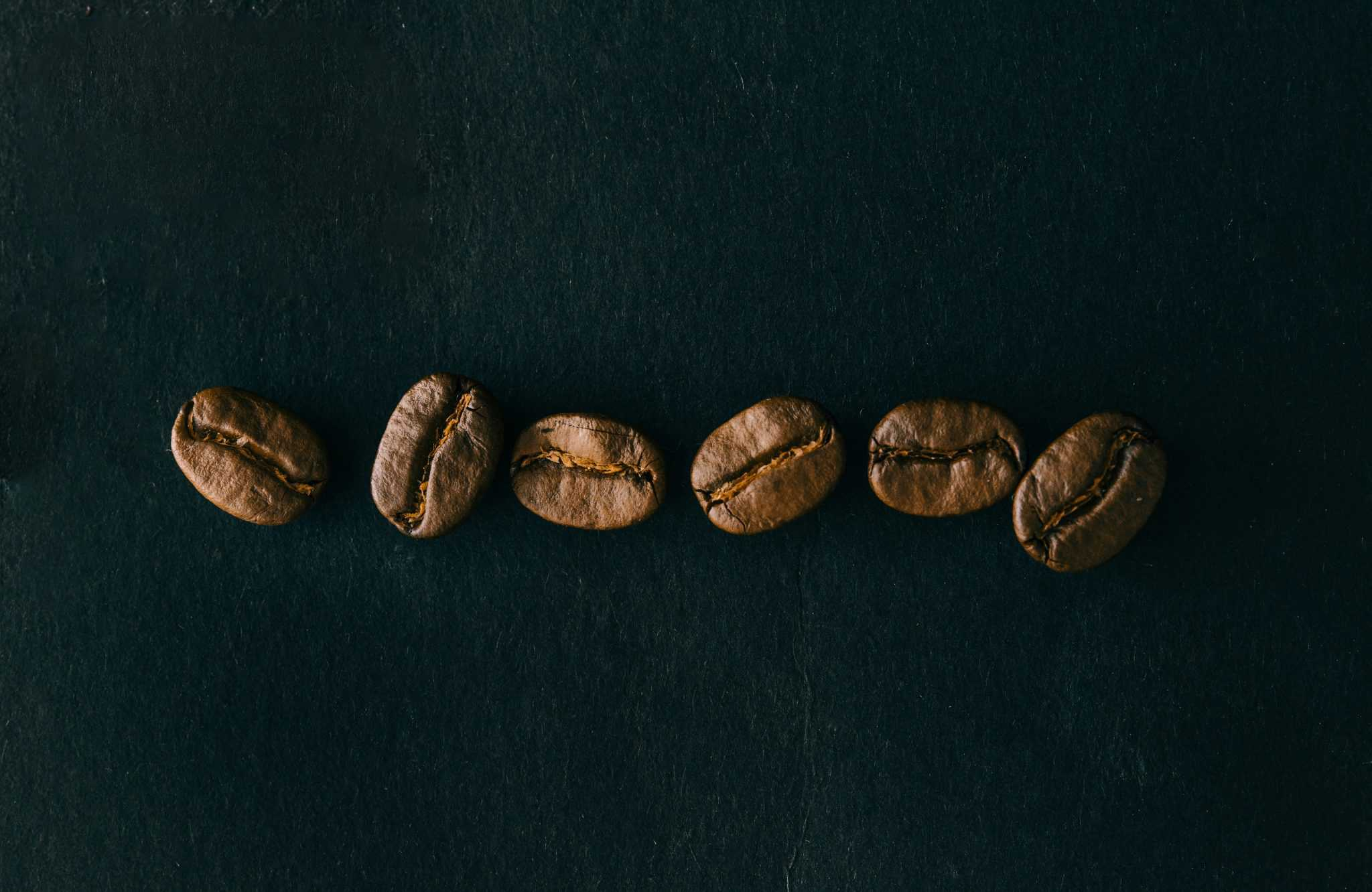Coffee beans in a row on black background