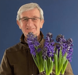 Alan Down of Down to Earth holding purple flowers on a blue background