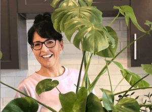 Ellen Mary of Ellen Mary gardening smiling behind tall house plant