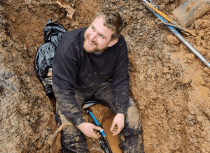 Kev of An English Homestead sat in a trench smiling