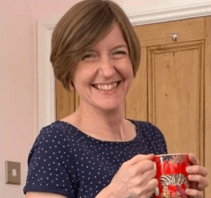 Catherine Hughes of Growing Family smiling and holding a mug