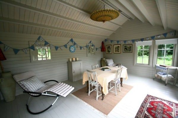 white and airy shed interior with table, bunting and reclining chair