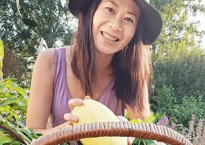 Jo Jo Yee of Jo Jo Garden Cook Smiling holding a vegetable