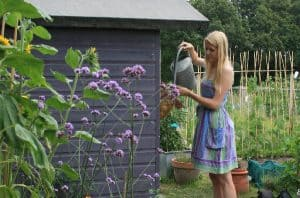 Katie of Lavender & Leeks watering plants next to a shed